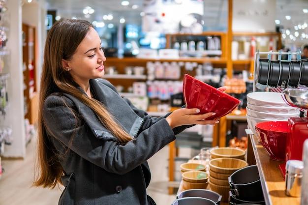 Jonge mooie vrouw die diner gebruiksvoorwerpen plaat gerechten kiest in een winkel supermarkt winkel.