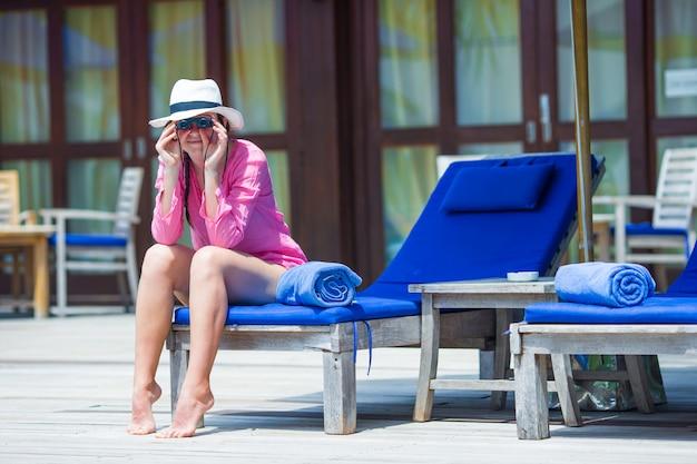 Jonge mooie vrouw die door verrekijkers zwembad kijkt