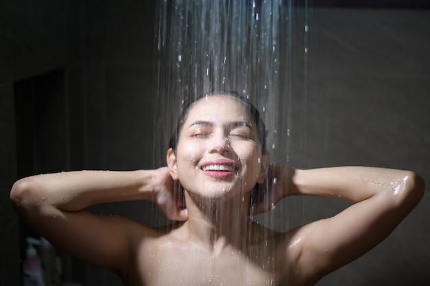 Jonge mooie vrouw die douche in een badkamers thuis neemt