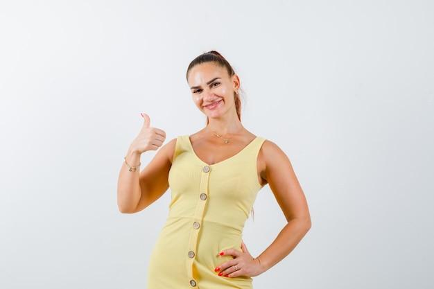 Jonge mooie vrouw die duim in kleding toont en blij kijkt. vooraanzicht.