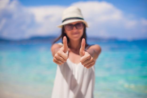 Jonge mooie vrouw die duimen op het strand toont