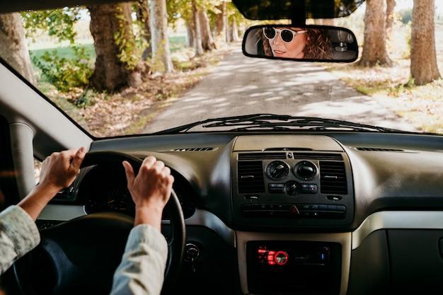 Jonge mooie vrouw die een auto drijft. reizen concept. uitzicht van binnenuit. pad van bomen weg