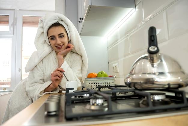 Jonge mooie vrouw die een badjas draagt en koffie drinkt, ontspant zich in de keuken, vóór de werkdag. levensstijl