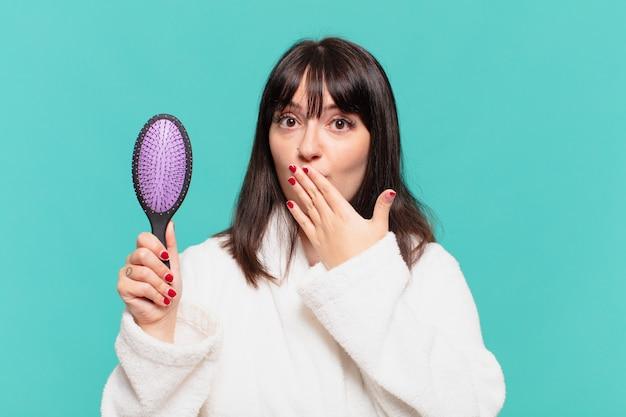 Jonge mooie vrouw die een bange uitdrukking van een badjas draagt en een haarborstel vasthoudt