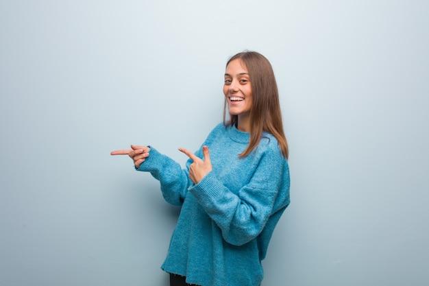 Jonge mooie vrouw die een blauwe sweater draagt die aan de kant met vinger richt
