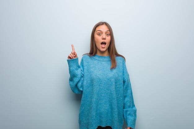 Jonge mooie vrouw die een blauwe sweater draagt die aan de kant richt