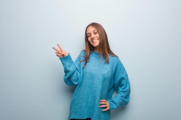 Jonge mooie vrouw die een blauwe sweater draagt die een gebaar van overwinning doet