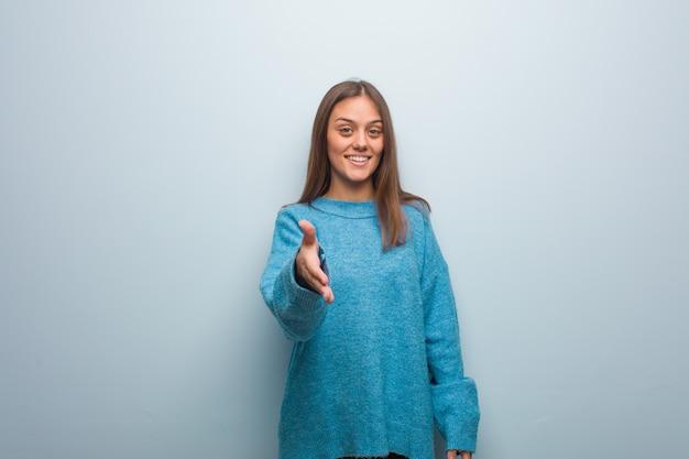 Jonge mooie vrouw die een blauwe sweater draagt die iemand bereikt te begroeten