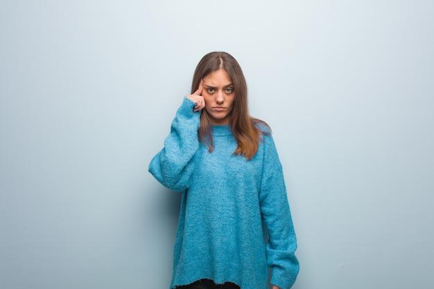 Jonge mooie vrouw die een blauwe sweater draagt die over een idee nadenkt