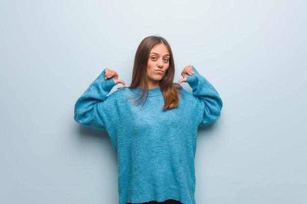 Jonge mooie vrouw die een blauwe sweater draagt die vingers richt, te volgen voorbeeld