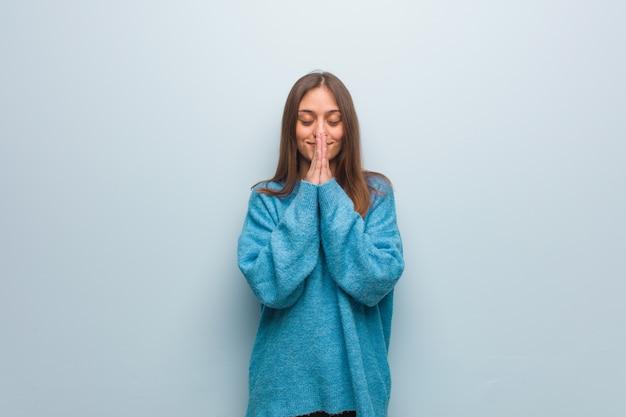 Jonge mooie vrouw die een blauwe sweater draagt die zeer gelukkig en zeker bidt