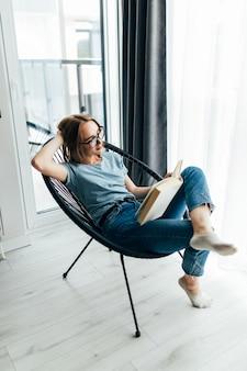 Jonge mooie vrouw die een boek leest en thuis op een comfortabele stoel zit