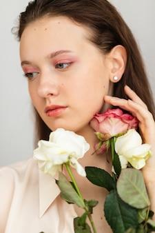 Jonge mooie vrouw die een bos rode rozen ruikt. mode interieur foto van mooie lachende vrouw met donker haar met een groot boeket rode rozen in valentijnsdag