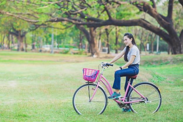 Jonge mooie vrouw die een fiets in een park berijdt.