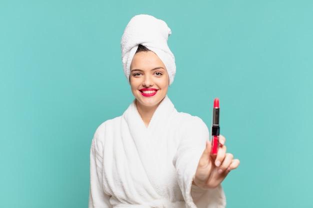 Jonge mooie vrouw die een gelukkige uitdrukking van een badjas en een lippenstift draagt