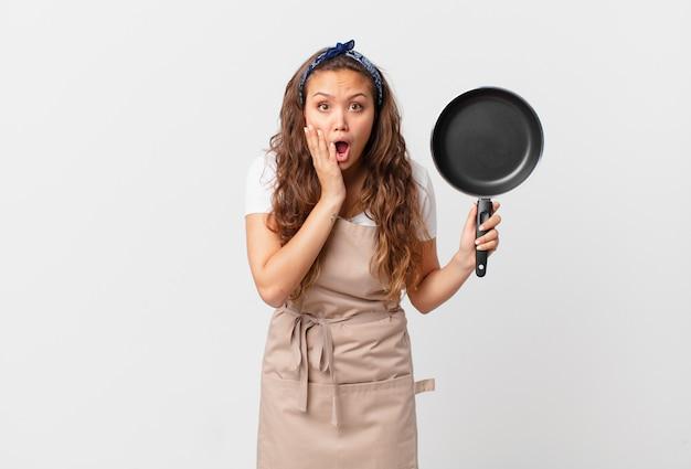 Jonge mooie vrouw die een geschokt en bang chef-kokconcept voelt en een pan vasthoudt