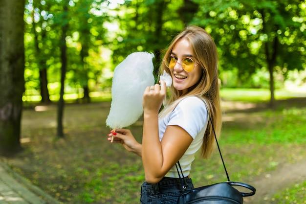 Jonge mooie vrouw die een gesponnen suiker in park eet