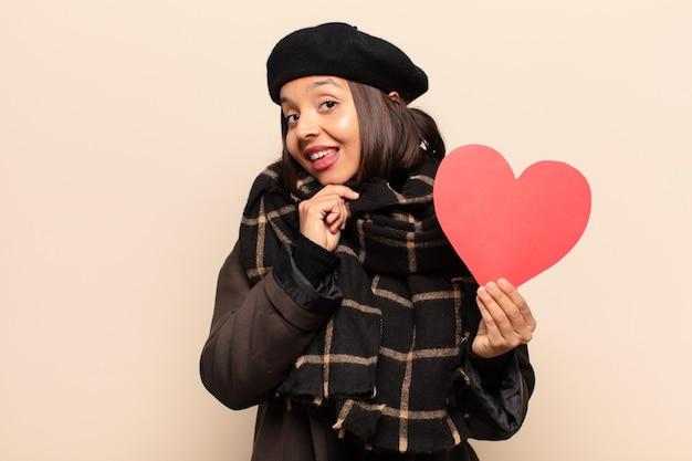 Jonge mooie vrouw die een hartkaart houdt
