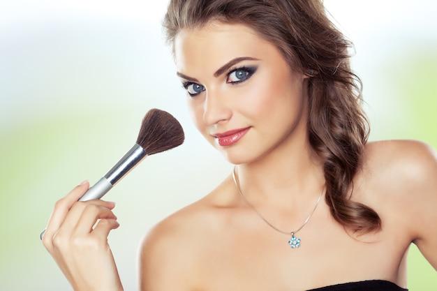Jonge mooie vrouw die een make-upborstel gebruikt