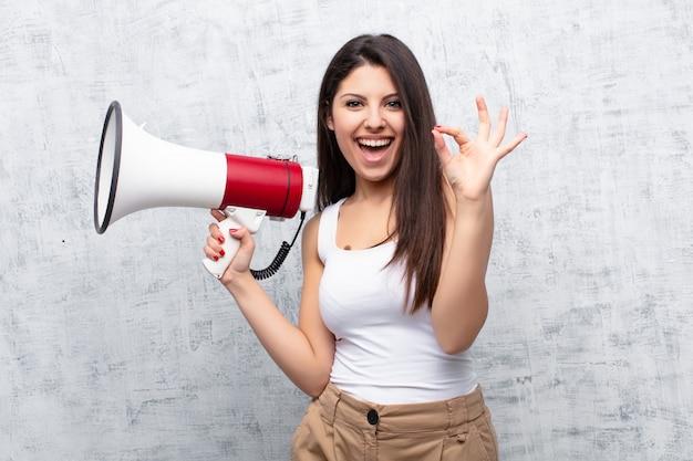Jonge mooie vrouw die een megafoon houdt tegen cementmuur