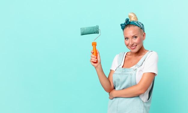 Jonge mooie vrouw die een muur schildert met een roller