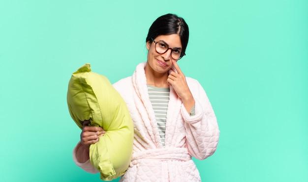 Jonge mooie vrouw die een oogje in het zeil houdt, niet vertrouwt, toekijkt en alert en waakzaam blijft. pyjama's concept