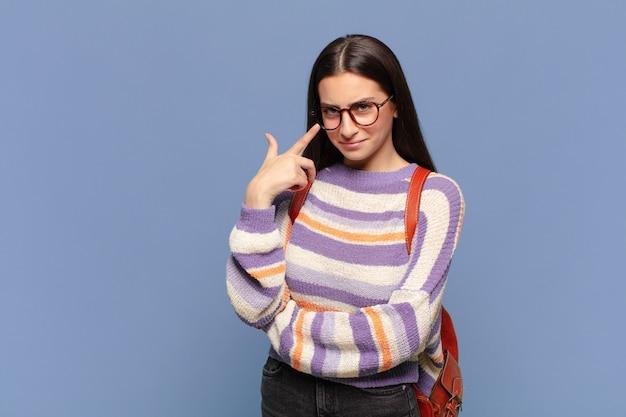 Jonge mooie vrouw die een oogje in het zeil houdt, niet vertrouwt, toekijkt en alert en waakzaam blijft. student concept