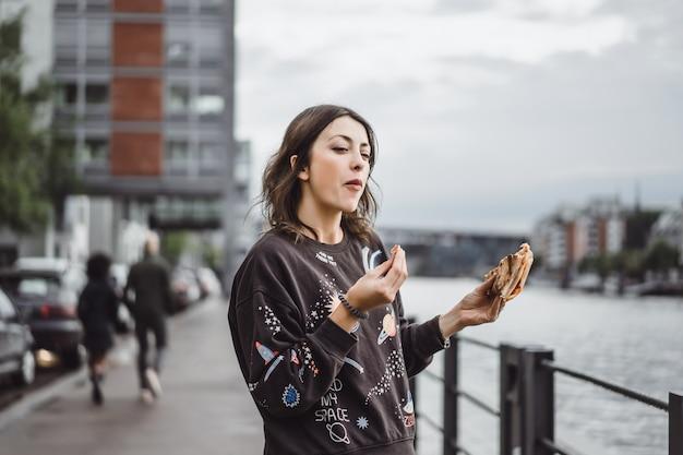 Jonge mooie vrouw die een plak van pizza op stadsstraat eet