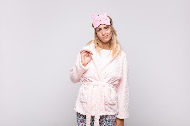 Jonge mooie vrouw die een pyjama draagt, er arrogant, succesvol, positief en trots uitziet, wijzend naar zichzelf