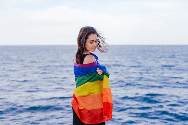 Jonge mooie vrouw die een regenboog vrolijke vlag in openlucht houdt