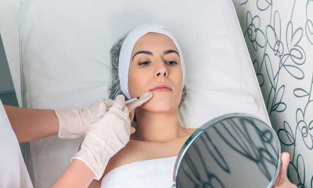 Jonge mooie vrouw die een schoonheidslippenbehandeling in een spiegel kijkt. geneeskunde, gezondheidszorg en schoonheidsconcept.