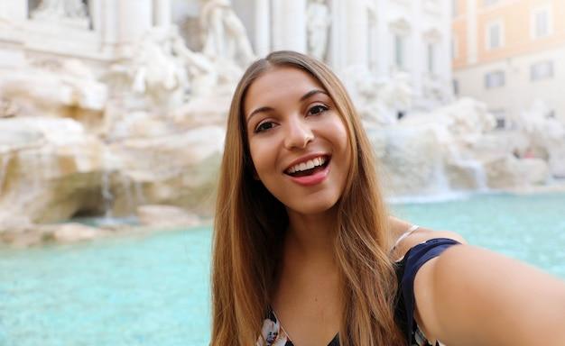 Jonge mooie vrouw die een selfie neemt bij de trevifontein