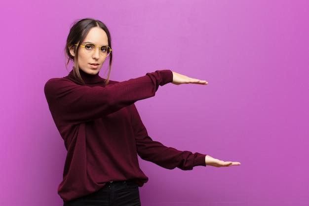 Jonge mooie vrouw die een voorwerp met beide handen op zijexemplaarruimte houdt, een voorwerp over purpere muur toont, aanbiedt of adverteert