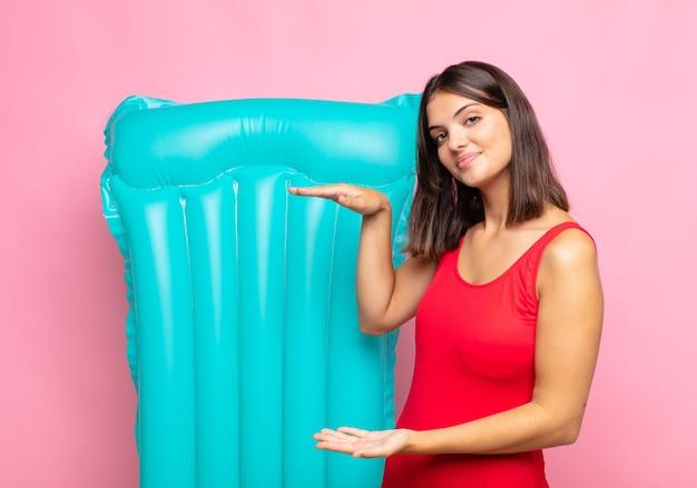 Jonge mooie vrouw die een voorwerp met beide handen op zijexemplaarruimte houdt, een voorwerp toont, aanbiedt of adverteren