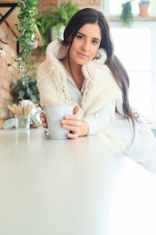 Jonge mooie vrouw die een warme drank in de keuken drinkt