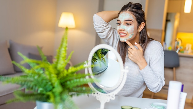Jonge mooie vrouw die eigengemaakt gezichtsmasker i thuis toepast.