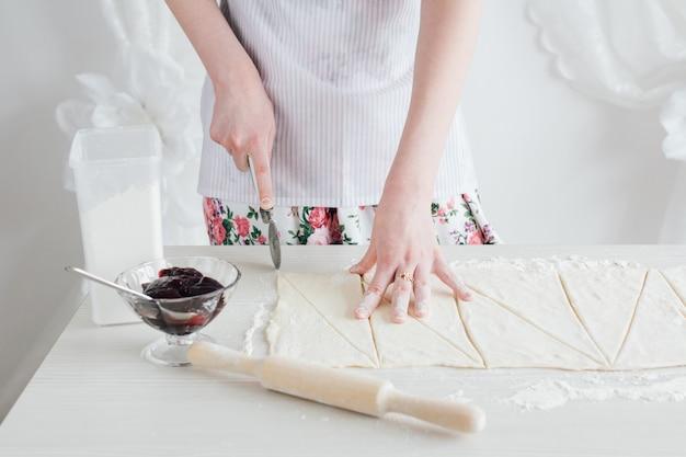 Jonge mooie vrouw die eigengemaakte croissants voorbereidt