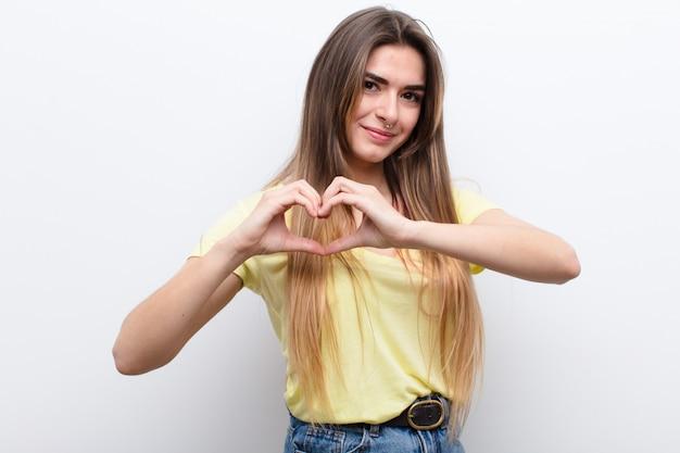 Jonge mooie vrouw die en gelukkig, leuk, romantisch en in liefde glimlacht voelt, die hartvorm met beide handen maakt