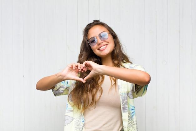 Jonge mooie vrouw die en gelukkig, leuk, romantisch en verliefd glimlacht voelt en hartvorm met beide handen maakt