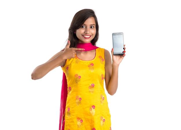Jonge mooie vrouw die en leeg scherm smartphone of gsm of tablet telefoon op een wit houdt.