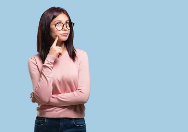 Jonge mooie vrouw die en omhoog kijkt denkt, verward over een idee