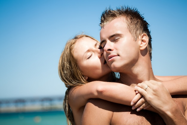 Jonge mooie vrouw die en van rug haar glimlachende vriend met blauwe overzees en zandig strand bij achtergrond omhelst kust