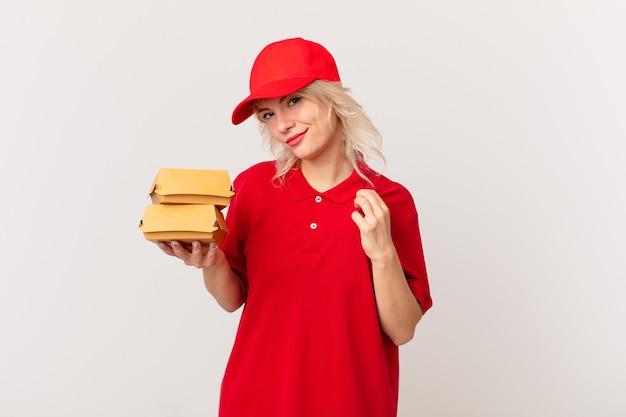 Jonge mooie vrouw die er arrogant, succesvol, positief en trots uitziet. hamburger bezorgconcept