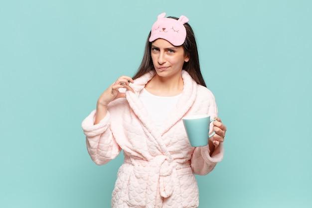 Jonge mooie vrouw die er arrogant, succesvol, positief en trots uitziet, wijzend naar zichzelf. wakker worden met pyjama's concept