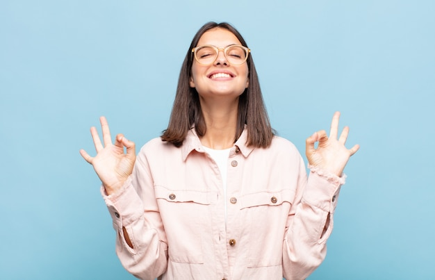 Jonge mooie vrouw die er geconcentreerd uitziet en mediteert, zich tevreden en ontspannen voelt, nadenkt of een keuze maakt