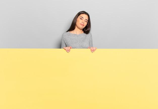 Jonge mooie vrouw die er gelukkig en vriendelijk uitziet, lacht en je met een positieve houding aankijkt. kopieer ruimte om uw concept te plaatsen