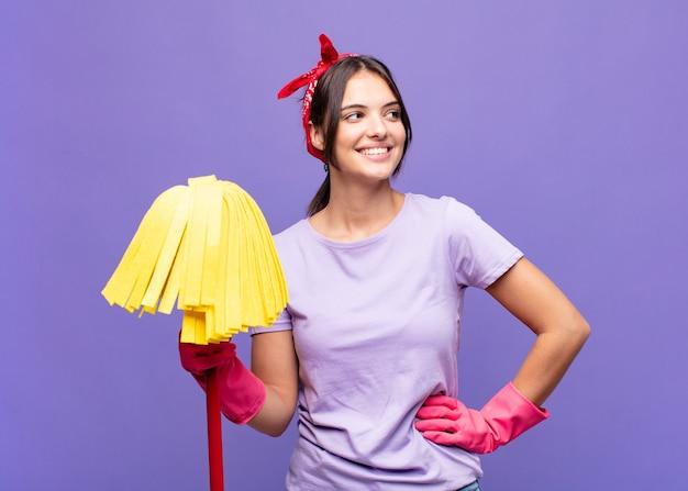 Jonge mooie vrouw die er gelukkig, vrolijk en zelfverzekerd uitziet, trots lacht en naar de zijkant kijkt met beide handen op de heupen