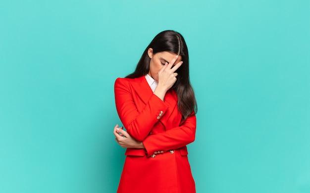 Jonge mooie vrouw die er gestrest, beschaamd of overstuur uitziet, met hoofdpijn, gezicht bedekt met de hand. bedrijfsconcept
