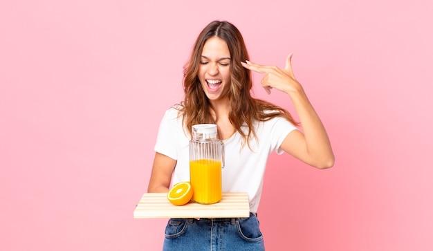 Jonge mooie vrouw die er ongelukkig en gestrest uitziet, zelfmoordgebaar maakt een pistoolteken en houdt een dienblad met een sinaasappelsap vast