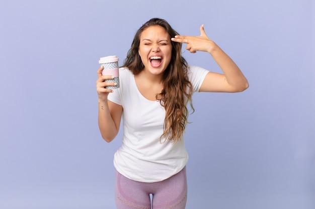 Jonge mooie vrouw die er ongelukkig en gestrest uitziet, zelfmoordgebaar maakt een pistoolteken en houdt een kopje koffie vast